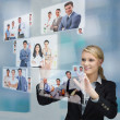Blonde businesswoman selecting image from digital interface — Stock Photo