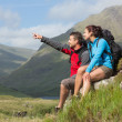 Couple taking a break after hiking uphill with man pointing — Stock Photo #31462417