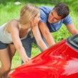 Happy couple pushing their broken down car — Stock Photo