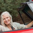 Smiling mature woman posing in red convertible — Stock Photo