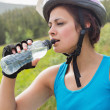 Fit woman wearing bike helmet drinking water — Stock Photo