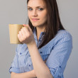 Smiling pretty brunette holding cup of coffee — Stock Photo