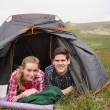 Happy couple lying in their tent after a hike and looking at camera — Stock Photo