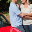 Stock Photo: Cheerful mature couple hugging against their red cabriolet