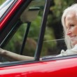 Cheerful mature woman driving red convertible — Stock Photo #31463121