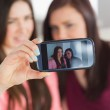 Two smiling girls sitting on a sofa taking a photo of themselves with a mobile phone — Stock Photo #31463213