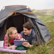 Happy couple lying in their tent and using digital tablet — Stock Photo