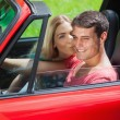Happy blonde kissing her boyfriend in red cabriolet — Stock Photo