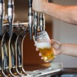 Stock Photo: Barmans arms pulling pint of beer