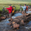 Couple crossing a stream holding their mountain bikes — Stock Photo