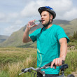 Fit man leaning on his mountain bike drinking water — Stock Photo