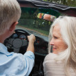 Stock Photo: Rear view of happy mature couple going for ride together