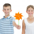 Smiling brother and sister playing with pinwheel — Stock Photo