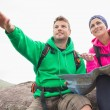 Couple using map and compass sitting on a rock with man pointing — Stock Photo