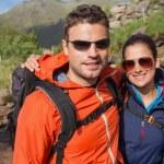 Couple wearing rain jackets and sunglasses smiling at camera — Stock Photo