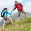 Stock Photo: Attractive hiker helping his girlfriend uphill