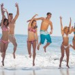 Happy friends jumping on the beach — Stock Photo #31464217