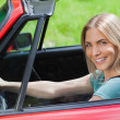 Cheerful woman driving red cabriolet — Stock Photo