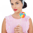 Thoughtful black hair model holding a colored lollipop — Stock Photo