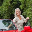 Cheerful mature woman getting off her convertible — Stock Photo #31464363