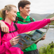 Athletic couple in hooded jumpers on a hike holding map — Stock Photo