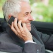 Cheerful mature businessman on the phone driving expensive cabriolet — Stock Photo