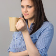 Pensive pretty brunette holding cup of coffee — Stock Photo