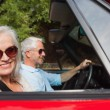 Side view of smiling mature couple driving red cabriolet — Stock Photo