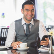 Businessman in a restaurant holding phone — Stock Photo