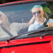 Happy mature couple in red cabriolet — Stock Photo