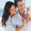 Smiling couple embracing each other on the beach — Stock Photo