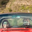 Front view of smiling couple in red cabriolet — Stock Photo #31465393
