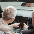 Business people working together on laptop in classy cabriolet — Stock Photo