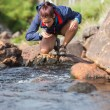 Hiker bending to take a drink from the stream — Photo