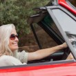 Happy mature woman with sunglasses driving red convertible — Stok fotoğraf