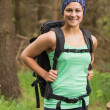 Pretty woman standing in a forest on a hike — Stock Photo