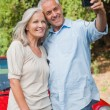 Smiling mature couple taking pictures of themselves — Stock Photo