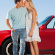 Cute couple kissing against their red cabriolet — Stock Photo