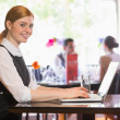 Happy businesswoman typing on laptop while smiling at camera — Stock Photo #31466687