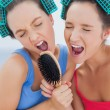 Friends in hair rollers holding hairbrush — Stock Photo #31466927