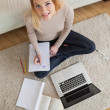 Happy woman doing homework and sitting on floor using laptop — Stock Photo