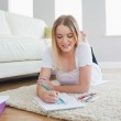 Smiling blonde woman lying on floor sketching on paper — Stock Photo #31467115