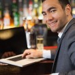 Smiling businessman working on his laptop while having a drink — Stock Photo