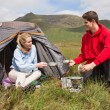 Cheerful couple cooking outdoors on camping trip — Stock Photo #31467213