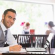 Happy businessman writing while smiling at camera — Stock Photo