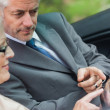 Partners working together on tablet in classy convertible — Stockfoto