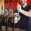 Handsome barkeeper pulling a pint of beer — Stock Photo