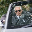 Stock Photo: Cheerful mature businessman driving classy cabriolet