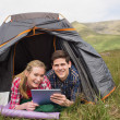 Smiling couple lying in their tent and using digital tablet — Stock Photo