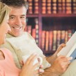 Happy couple reading books and drinking coffee in a reading room — Stock Photo